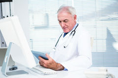 Doctor using digital tablet by computer Stock Photos