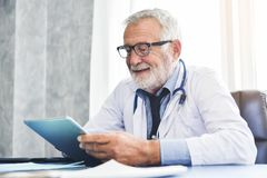 Doctor is using digital tablet computer. Happy Senior Male Doctor is using digital tablet computer in the Medical room. Health concept. Technology Royalty Free Stock Photography