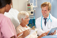 Doctor Using Digital Tablet In Consultation With Senior Patient Stock Photos