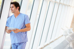 Doctor Using Digital Tablet In Corridor Of Modern Hospital Royalty Free Stock Photos