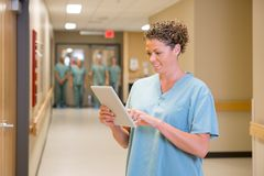 Doctor Using Digital Tablet In Hospital Corridor stock image