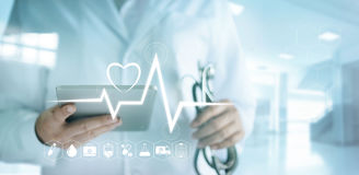 Doctor using digital tablet with medical icon and heartbeat rate Royalty Free Stock Photo