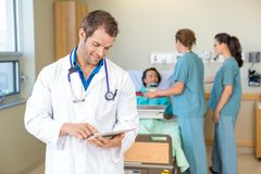 Doctor Using Digital Tablet While Nurses Serving Royalty Free Stock Images