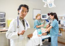 Doctor Using Digital Tablet While Nurses Treating Stock Photos