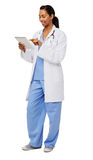 Doctor Using Digital Tablet Over White Background. Full length of female doctor using digital tablet isolated over white background. Vertical shot Royalty Free Stock Photo