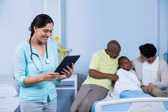 Doctor using digital tablet while parents interacting with patient Royalty Free Stock Photos
