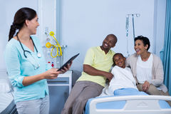 Doctor using digital tablet while parents interacting with patient Royalty Free Stock Photography