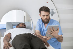 Doctor Using Digital Tablet By Patient Lying On CT Scanner royalty free stock photos