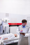 Doctor using digital tablet and patient lying on x ray machine Royalty Free Stock Photography