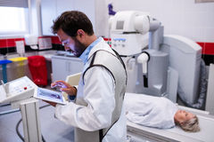 Doctor using digital tablet and patient lying on x ray machine Stock Photos