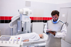 Doctor using digital tablet and patient lying on x ray machine Stock Images