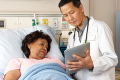 Doctor Using Digital Tablet Talking With Senior Patient Royalty Free Stock Photo