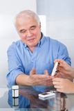 Doctor using lancelet on senior man Stock Image