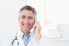 Doctor using landline phone in clinic Stock Photography