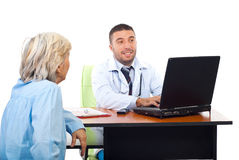 Doctor using laptop while converse with patient Royalty Free Stock Image