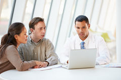 Doctor Using Laptop Discussing Treatment With Patients Royalty Free Stock Photography