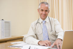 Doctor using laptop in doctor's office. Smiling Royalty Free Stock Photography