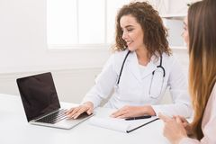 Doctor using laptop in office, making patient`s anamnesis stock photo