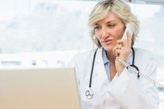 Doctor using laptop and phone in medical office Royalty Free Stock Photos