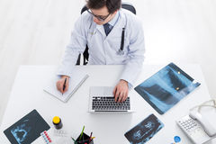 Doctor using laptop and reflecting. Topview of doctor sitting at office desk with x-rays and other items, using laptop and reflecting in journal Royalty Free Stock Photo