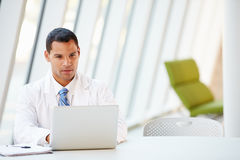 Doctor Using Laptop Sitting At Desk In Modern Hospital Stock Photo