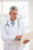 Doctor using laptop smiling to camera Royalty Free Stock Photography