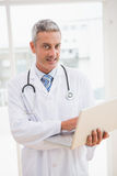 Doctor using laptop smiling to camera Royalty Free Stock Image