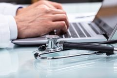 Doctor Using Laptop. With Stethoscope On Desk stock images