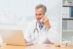 Doctor using laptop and talking on phone at desk Stock Photo