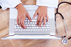 Doctor using laptop on wooden desk Stock Photo