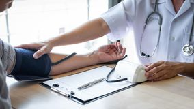 Doctor using a measuring blood pressure checking patient with examining, presenting results symptom and recommend treatment method stock photos