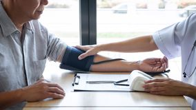 Doctor using a measuring blood pressure checking patient with examining, presenting results symptom and recommend treatment method royalty free stock photography