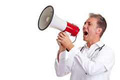 Doctor using a megaphone. Senior doctor shouting into a big megaphone Royalty Free Stock Images