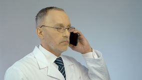 Doctor using mobile phone, dialing number, calling patient to arrange meeting. Stock footage stock video
