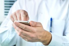 Doctor using mobile phone. Person in white coat. Doctor using mobile phone. Person in white coat typing smartphone Stock Photo