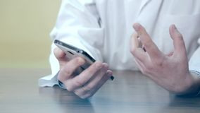 Doctor using a mobile phone and a tablet. A male doctor using electronic devices. Doctor using a mobile phone and a tablet. A male doctor using electronic stock video footage