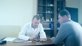 Doctor using a mobile phone and a tablet. A male doctor using electronic devices. Doctor using a mobile phone and a tablet. A male doctor using electronic stock footage