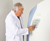 Doctor using MRI machine. Doctor using buttons of a MRI machine in radiology Royalty Free Stock Photo