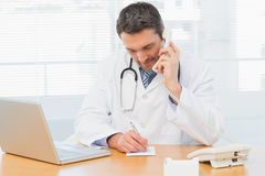 Doctor using phone while writing notes at medical office. Concentrated male doctor using phone while writing notes by laptop at the medical office Stock Photography