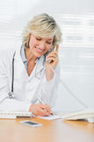 Doctor using phone while writing notes at medical office Stock Photography