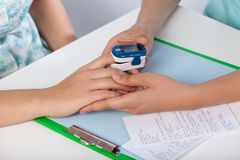 Doctor using pulse oximeter. To examine patient Royalty Free Stock Photos