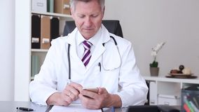 Doctor is using smart phone. Doctor working at the hospital and using smart phone stock video