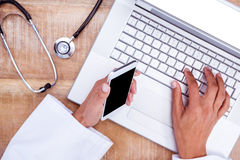 Doctor using smartphone and laptop on wooden desk Stock Photo