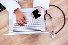 Doctor using smartphone on wooden desk Royalty Free Stock Photo