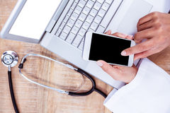 Doctor using smartphone on wooden desk Royalty Free Stock Image