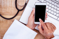 Doctor using smartphone on wooden desk Stock Photo