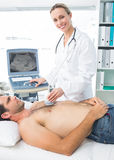 Doctor using sonogram on male patient Royalty Free Stock Images