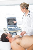 Doctor using sonogram on male patient Stock Photography
