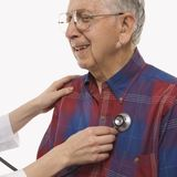 Doctor using stethescope. Mid-adult Caucasian female hands listening  to elderly Caucasian male's heart with stethoscope Stock Images