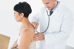 Doctor using stethoscope on back of patient Royalty Free Stock Photos